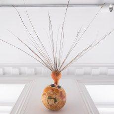 Melania Toma<br />Arousal Pumpkin<br />2021<br />pumpkin, wood varnish, oil pastel, glue pigments, palm leaves<br />116x171cm